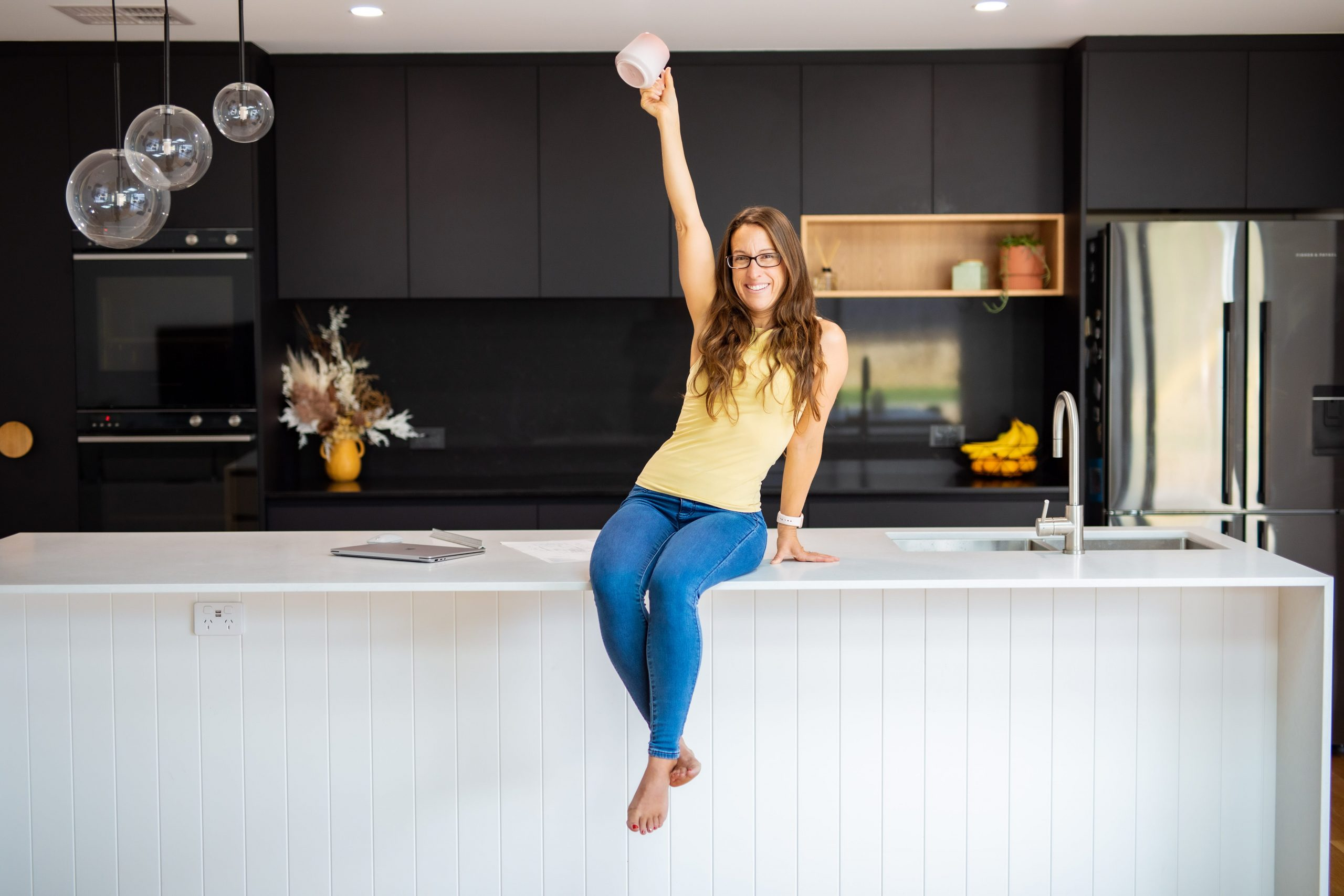 Woman sitting on kitchen table holding mug in the air posing for personal branding photography