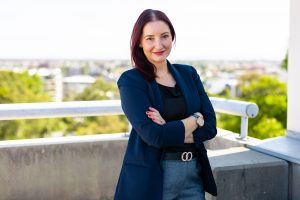 Business woman standing on a carpark rooftop posing for an example of How to Use Corporate Headshots On Your Website